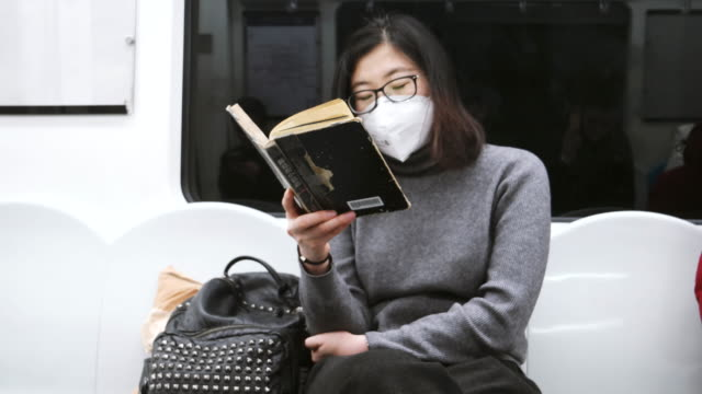 chinese woman seating in subway train wearing pollution mask / beijing, china - pollution mask stock videos & royalty-free footage