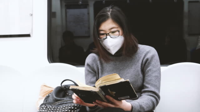 chinese woman seating on subway train wearing pollution mask / beijing, china - pollution mask stock videos and b-roll footage