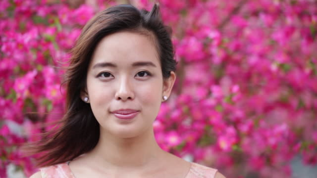 CU  Chinese woman smiling in front of pink flowers.