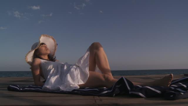 stockvideo's en b-roll-footage met chinese woman sunbathing - zonnejurk