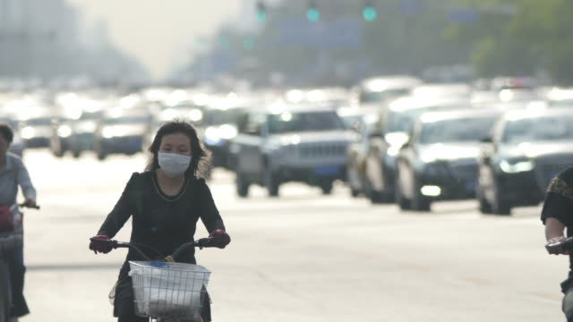 chinese woman wearing mask cycling in traffic in beijing, china - smog video stock e b–roll