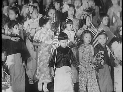 Chinese women in traditional garb parade down city street twirling batons and playing drums / Chinese children parade down city street carrying...