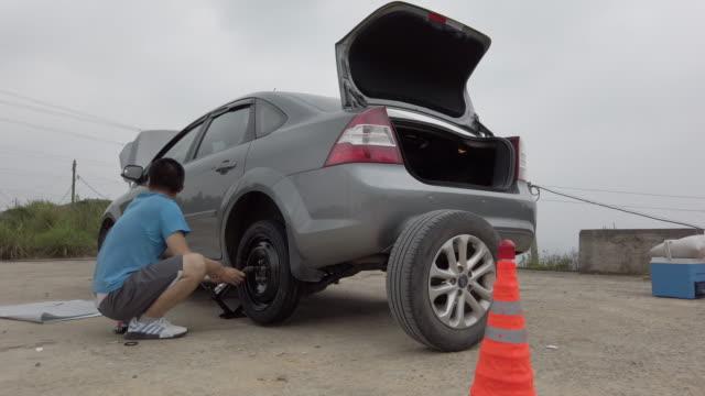 vídeos de stock, filmes e b-roll de chinese young man changing car tires on the roadside - margem de estrada