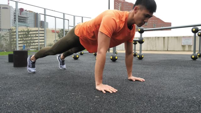 chinese young man exercising on cloudy day, doing push ups. - london marathon stock videos & royalty-free footage