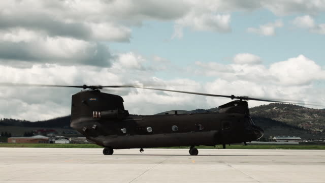 chinook helicopter at an airfield with rotors spinning. - helicopter rotors stock videos and b-roll footage