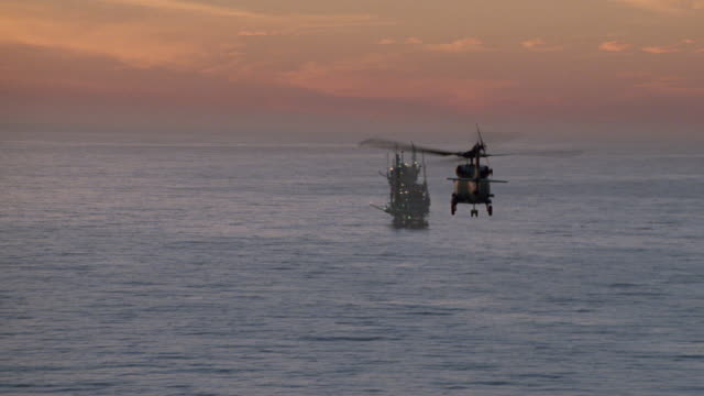 a chinook helicopter flies towards an offshore drilling platform. - south pacific ocean stock videos & royalty-free footage