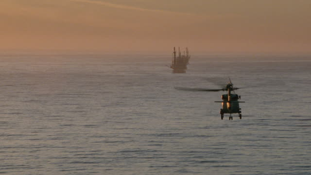 a chinook helicopter flies towards an offshore oil rig. - south pacific ocean stock videos & royalty-free footage