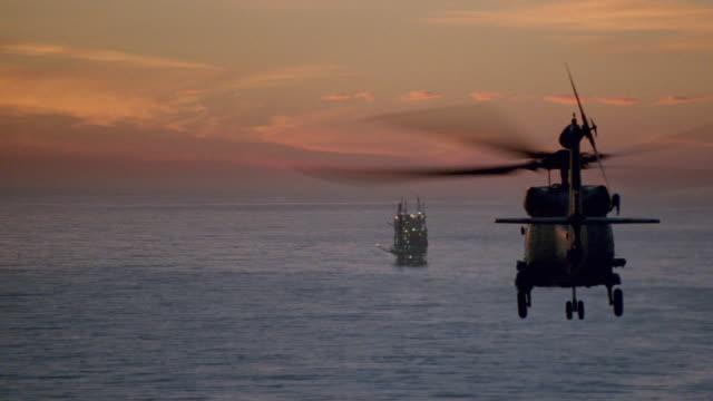 a chinook helicopter flying towards an offshore drilling platform. - south pacific ocean stock videos & royalty-free footage