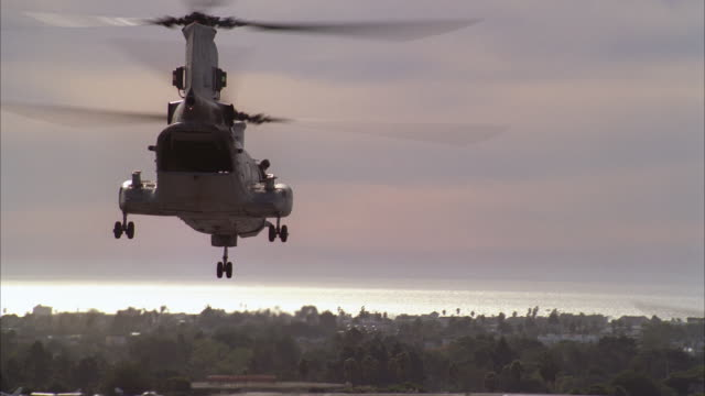 A Chinook helicopter takes off from a runway at the Santa Monica Airport as two other Chinooks join it.