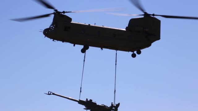 chinook helicopters deliver m777 howitzers by sling load to yakima training center washington army national guard 24 june 2019 - militärmanöver stock-videos und b-roll-filmmaterial