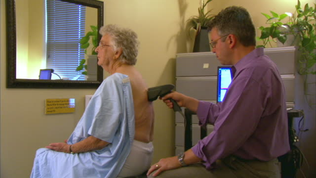 ms chiropractor examining patient, head of st. margaret's bay, nova scotia, canada - examination gown stock videos and b-roll footage