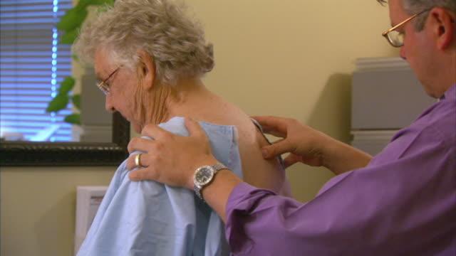 ms chiropractor examining patient, head of st. margaret's bay, nova scotia, canada - 人の背中点の映像素材/bロール