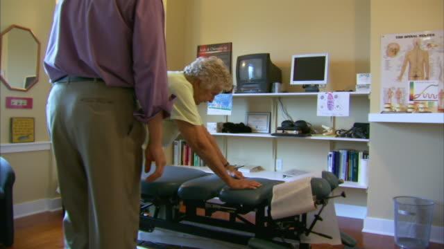 stockvideo's en b-roll-footage met ms chiropractor examining patient, head of st. margaret's bay, nova scotia, canada - driekwartlengte