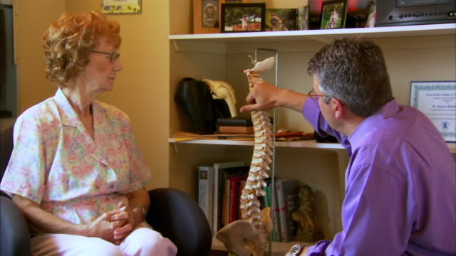 ms chiropractor talking with patient, head of st. margaret's bay, nova scotia, canada - wirbelsäule mensch stock-videos und b-roll-filmmaterial
