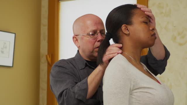 ms chiropractor treating female patient / manchester, vermont, usa - menschlicher hals stock-videos und b-roll-filmmaterial