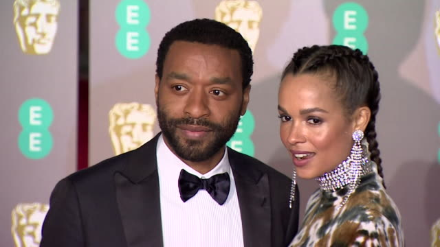 chiwetel ejiofor poses for photos with partner on red carpet at bafta film awards at royal albert hall - red carpet event stock videos & royalty-free footage