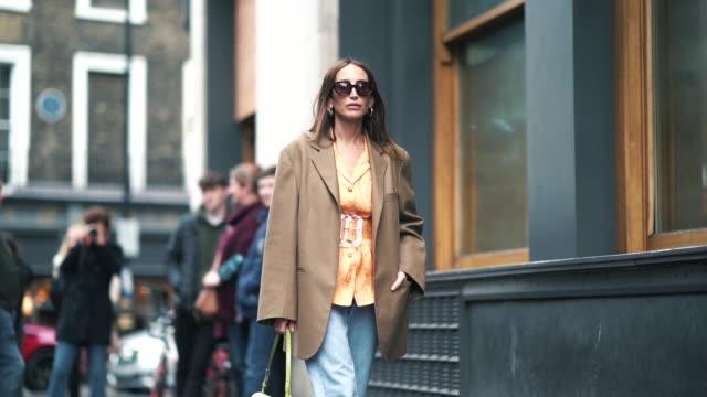 Chloe Harrouche wears a brown blazer jacket an orange shirt a large plastic tranparent belt blue pants a green bag red shoes sunglasses during London...
