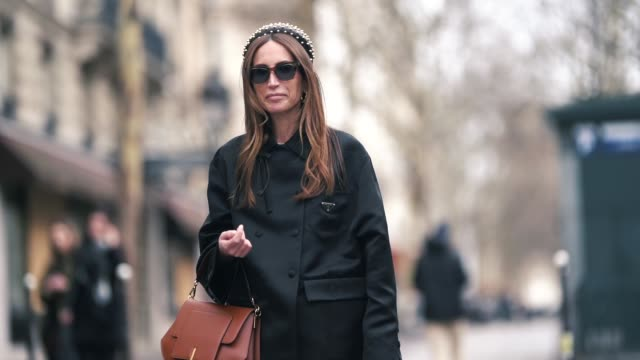 chloe harrouche wears a headband, a black jacket, a brown leather bag, shorts, black shoes, earrings, sunglasses, outside altuzarra, during paris... - shorts stock videos & royalty-free footage