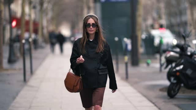 chloe harrouche wears a headband a black jacket a brown leather bag shorts black shoes earrings sunglasses outside altuzarra during paris fashion... - shorts stock-videos und b-roll-filmmaterial