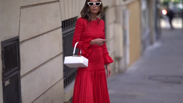 chloe harrouche wears a red dress and a white bag, outside altuzarra, during paris fashion week womenswear spring/summer 2019, on september 29, 2018... - street style stock videos & royalty-free footage
