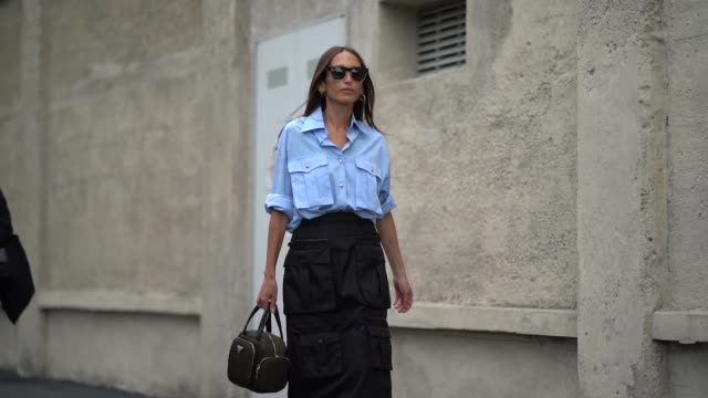 chloe harrouche wears sunglasses, a blue shirt, a black skirt with cargo pockets, a prada green khaki bag, outside the prada show during milan... - street style stock videos & royalty-free footage
