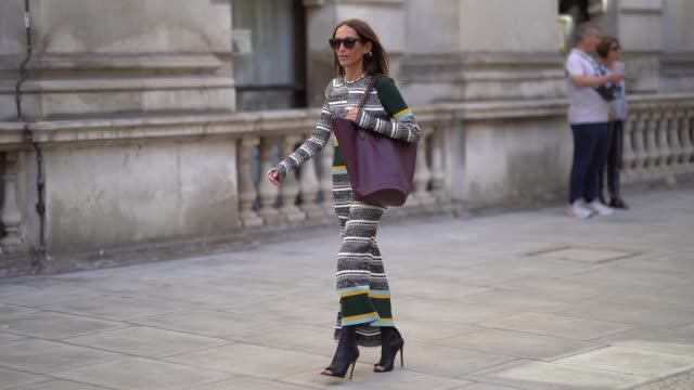 stockvideo's en b-roll-footage met chloe harrouche wears sunglasses a gray and white striped dress a burgundy leather bag black heels shoes during london fashion week september 2019 on... - modeweek
