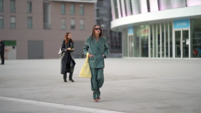 chloe harrouche wears sunglasses, an oversized green blazer jacket, a triangular yellow bag, flare pants, a golden necklace, outside jacquemus,... - menswear stock videos & royalty-free footage