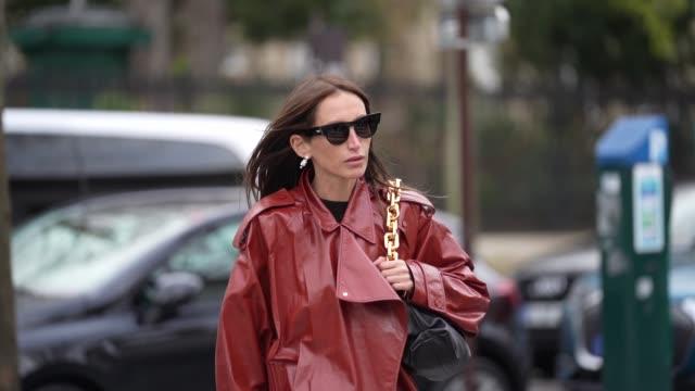 vídeos de stock e filmes b-roll de chloe harrouche wears sunglasses, earrings, a bottega veneta bag with a golden chain handle, a red leather trench long coat, black pants, black... - saco objeto manufaturado