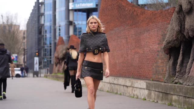 chloe lecareux wears a black leather cropped bare belly balmain top with knitted checked paterns, a black leather mini skirt, a bag, pointy boots,... - skirt stock videos & royalty-free footage