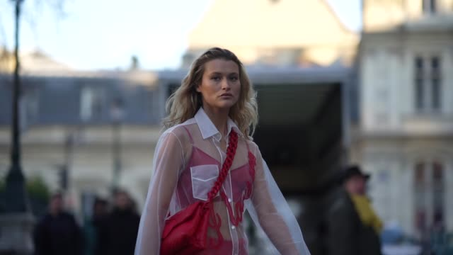 chloe lecareux wears a clear mesh shirt, a red quilted bag, red bras, red shiny glitter flared pants, shoes, outside viktor & rolf, during paris... - paris fashion week - haute couture spring/summer 2020点の映像素材/bロール