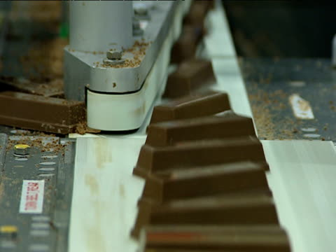 Chocolate bars are sorted along factory conveyer belt