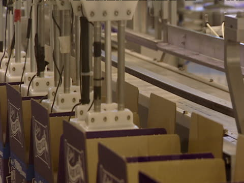 Chocolate bars in wrappers are transported up using suction in factory production line