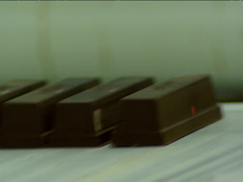 Chocolate bars on conveyer belt disappear between rollers in factory