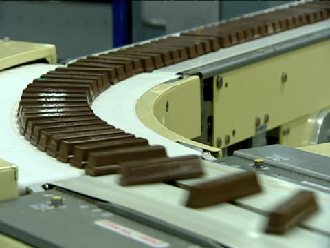 chocolate bars pass around bend along conveyer belt in factory - chocolate factory stock videos & royalty-free footage