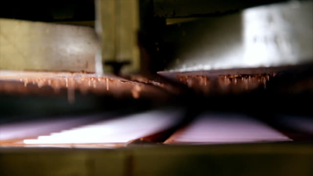 chocolate being squirted into pink chocolate moulds by a machine - chocolate factory stock videos & royalty-free footage