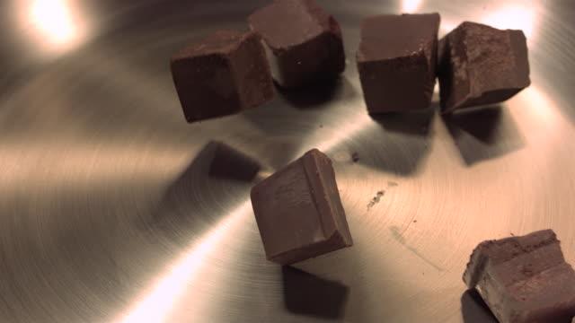 Chocolate blocks falling onto pan.
