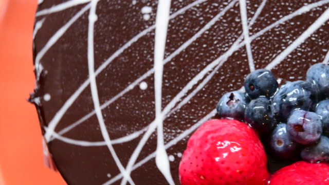 chocolate cake garnished with strawberries and blueberries - espositore per negozio video stock e b–roll