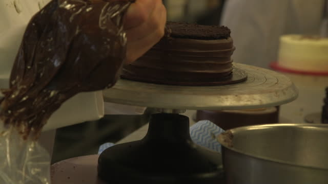 chocolate cake iced with chocolate icing on turntable at bakery of lola's cupcakes - record player stock videos & royalty-free footage