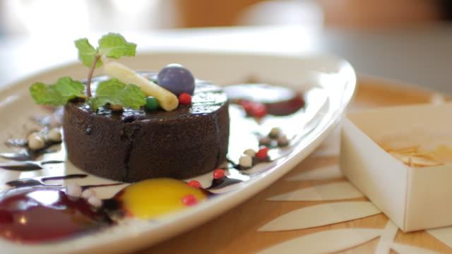 女性手の切断のケーキの上にチョコレート ケーキは、ドリー ショット右から左への動き - 連続するイメージ点の映像素材/bロール