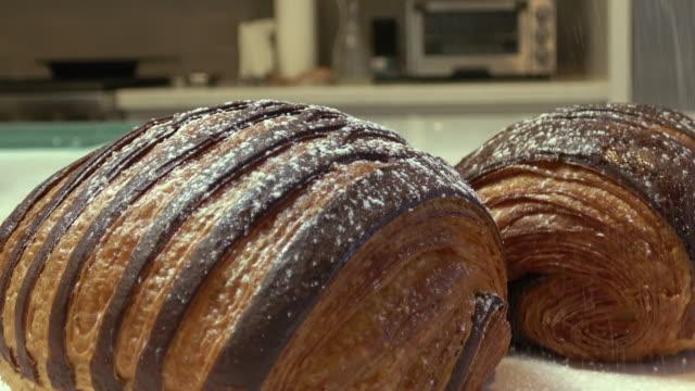 vídeos y material grabado en eventos de stock de croissants cubiertos de chocolate con azúcar en polvo - preparación de alimentos