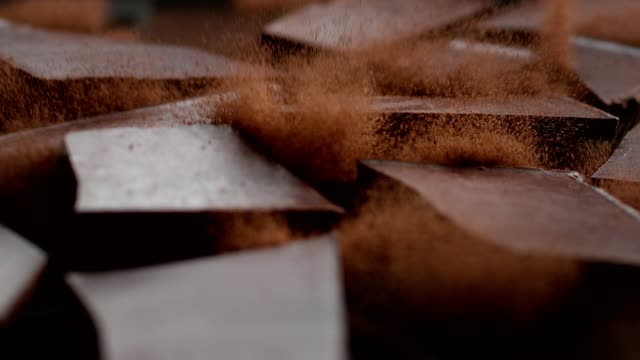 chocolate cubes cracking on cacao powder. cocoa explosions - dessert stock videos & royalty-free footage