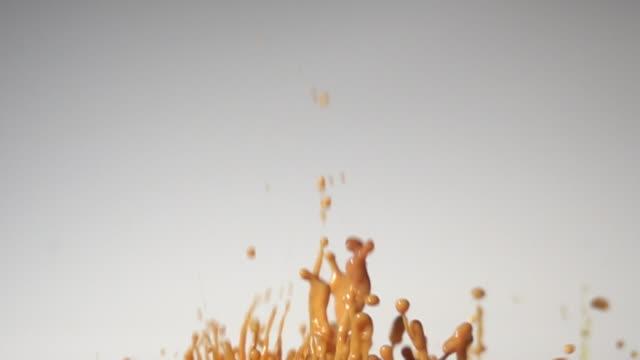 スローモーションで白い背景を持つチョコレートダンスの色 - はずむ点の映像素材/bロール