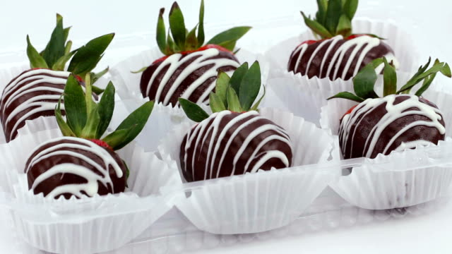 Chocolate dipped and drizzled strawberries in cup cake papers.