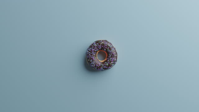 chocolate donut with sprinkles on a blue background - dessert topping stock videos & royalty-free footage