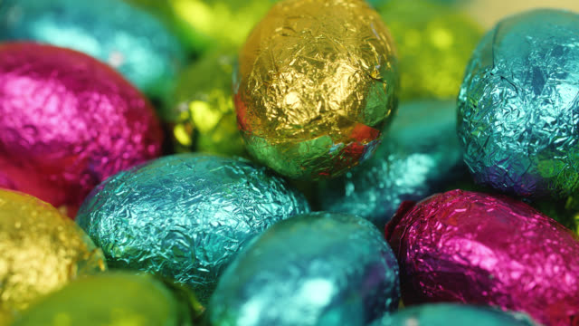 chocolate eggs wrapped in shiny foil slowly rotate - easter stock videos & royalty-free footage