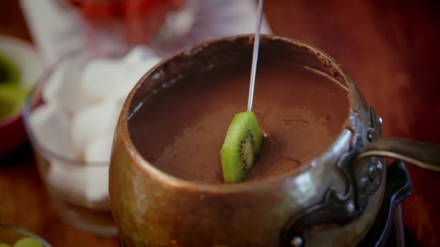 chocolate fondue in a pot served with fruits - kiwi fruit stock videos and b-roll footage