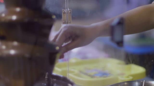vidéos et rushes de fontaine de chocolat avec des bonbons fondue tremper et de gouttes - belgique