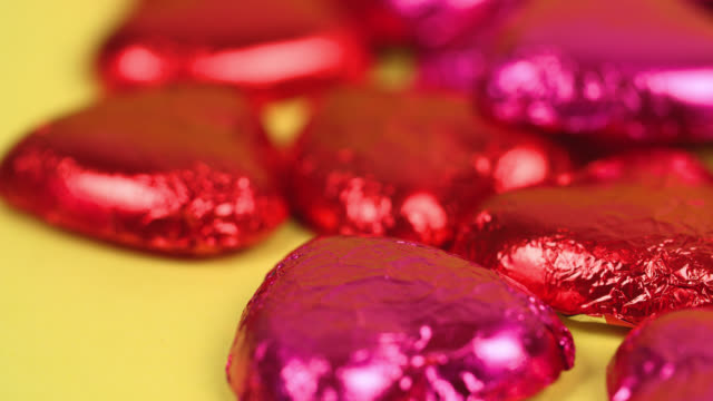 chocolate love hearts wrapped in shiny foil slowly revolve - valentines day stock videos & royalty-free footage