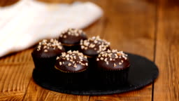 Chocolate muffin with crushed nuts on wooden background.