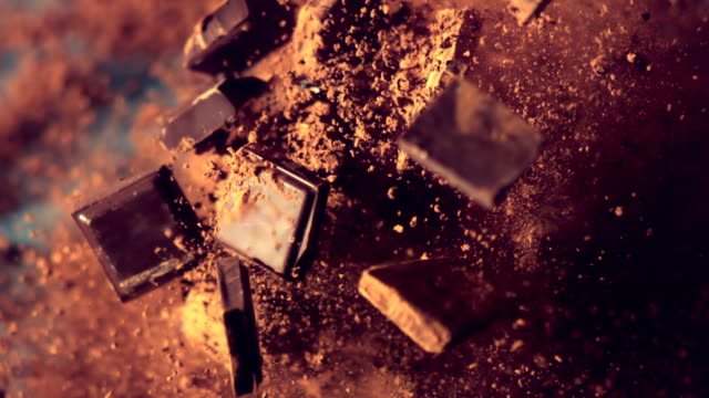 vídeos de stock e filmes b-roll de chocolate pieces falling down - gastrónomo
